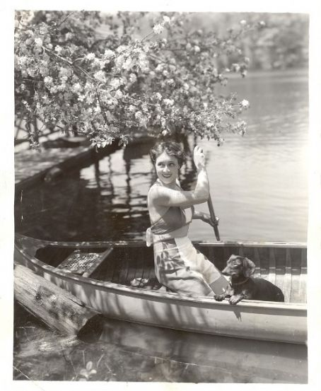 Irene Rich in a boat with a dachshund.